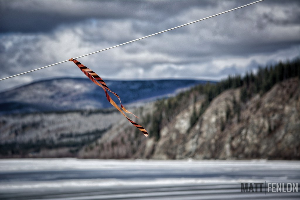 "This rope is attached to the yellow tripod on the ice, and is part of the annual ""Break Up"" event. When the tripod moves, ice on the Yukon River at Dawson has officially broken up."